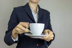 Jonge vrouw in wit overhemd en kostuum die een kop van koffie houden Bedrijfs concept royalty-vrije stock afbeelding
