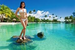 Jonge vrouw in witte bikini die zich op strand bevindt royalty-vrije stock fotografie