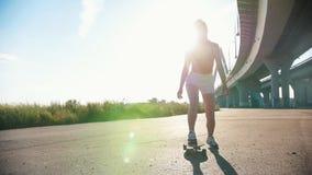 Jonge vrouw in witte borrels met aardige benen die skateboard berijden onder de stedelijke brug - helder zonlicht stock videobeelden