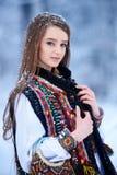 Jonge vrouw in witte geborduurde blouse en multicolored vest in openlucht op zonnige de winterdag stock afbeeldingen