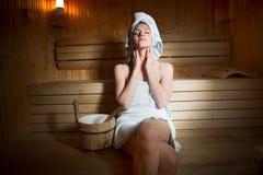 Jonge vrouw in witte handdoek die in Finse sauna liggen Stock Foto
