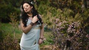 Jonge vrouw in witte kleding in de lentepark stock videobeelden
