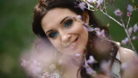 Jonge vrouw in witte kleding in de lentepark stock video
