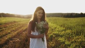 Jonge vrouw in witte kleding die zich in weide met boeket van bloemen bevinden die in de camera glimlachen stock footage