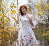 Jonge vrouw in witte kleding onder gele bladeren in de herfst Royalty-vrije Stock Foto