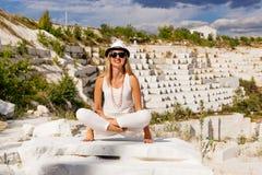 Jonge vrouw in witte kledingszitting in Lotus-positie, Padmasana inzake de achtergrond van de witte marmeren steengroeve Stock Foto's