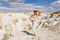 Jonge vrouw in witte kostuum en hoed in volledige lengte, marmeren steengroeve, wit marmer Royalty-vrije Stock Foto's