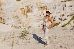 Jonge vrouw in witte kostuum en hoed in volledige lengte, marmeren steengroeve, wit marmer Royalty-vrije Stock Fotografie