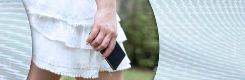 Jonge vrouw in witte rok met mobiele telefoon in haar hand Panoramische banner royalty-vrije stock fotografie