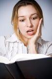 Jonge vrouw wordt verbaasd die door wat zij leest Royalty-vrije Stock Foto's