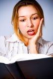 Jonge vrouw wordt verbaasd die door wat zij leest Stock Foto