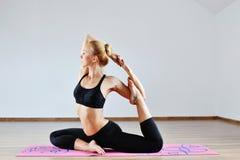 Jonge vrouw in yogapositie binnen Stock Foto's