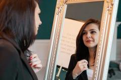 Jonge vrouw zelf die thuis bezinning in spiegel kijken stock afbeeldingen