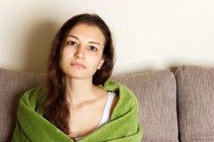 Jonge vrouw ziek of droevig die verpakt in deken en thuis op bank zitten die, blankly vooruit staren voelen Medisch en gezondheid stock afbeeldingen