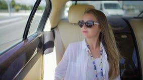 Jonge vrouw in zonnebril die door auto naar een andere stad reizen, luxelevensstijl stock footage