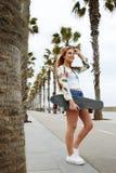 Jonge in vrouw in zonnebril die met haar longboard stellen die van goede dag in de zomer genieten Stock Afbeelding