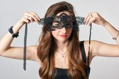 Jonge vrouw in zwart partijmasker stock afbeeldingen