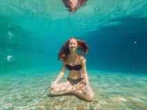 Jonge vrouw in zwarte bikini in yogapositie onderwater in het duiken aquarium, volledig geschoten lichaam, vooraanzicht stock foto's