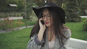 Jonge vrouw in zwarte hoed en glazen die op de mobiele telefoon in een stadspark spreken stock video