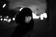 Jonge vrouw in zwarte laag bij de nachtstraat stock fotografie