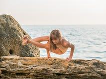 Jonge vrouw in zwempak het praktizeren yoga bij verbazende zonsopgang Fitness, sport, yoga en gezond levensstijlconcept Meisje stock foto