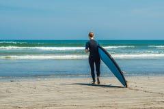 Jonge vrouw in zwempak met branding voor beginners klaar te surfen Positieve emoties stock afbeeldingen