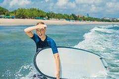 Jonge vrouw in zwempak met branding voor beginners klaar te surfen Positieve emoties stock afbeelding