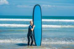 Jonge vrouw in zwempak met branding voor beginners klaar te surfen Positieve emoties stock foto's