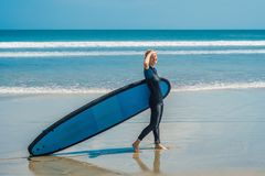 Jonge vrouw in zwempak met branding voor beginners klaar te surfen Positieve emoties royalty-vrije stock fotografie