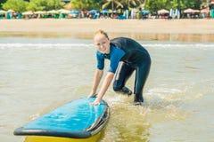 Jonge vrouw in zwempak met branding voor beginners klaar te surfen Positieve emoties royalty-vrije stock foto