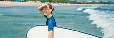 Jonge vrouw in zwempak met branding voor beginners klaar te surfen Positieve emotiesbanner, LANG FORMAAT stock afbeelding