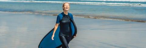 Jonge vrouw in zwempak met branding voor beginners klaar te surfen Positieve emotiesbanner, LANG FORMAAT stock foto