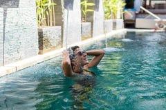 Jonge vrouw in zwempak in zwembad in schitterende toevlucht, luxevilla, het tropische eiland van Bali, Indonesië Royalty-vrije Stock Foto