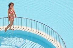 Jonge vrouw in zwempakgangen op richel die pools scheiden stock fotografie