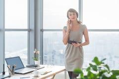 Jonge vrouwelijke adviseur die bedrijfsvraag in bureau hebben op het haar werk Secretaresse die op de slimme telefoon, het houden stock afbeelding