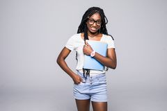 Jonge vrouwelijke Afrikaanse Amerikaanse student die in die glazen boeken houden op wit worden ge?soleerd stock foto