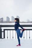 Jonge vrouwelijke agent die flexibiliteitsoefening voor benen doen vóór of na het lopen bij de verticale promenade van de sneeuww royalty-vrije stock foto's