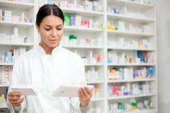 Jonge vrouwelijke apotheker die een tablet en een doos van medicijnen houden stock foto's