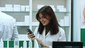 Jonge vrouwelijke apotheker texting berichten gebruikend mobiele telefoon, glimlachend en sprekend aan haar mannelijk colleauge royalty-vrije stock afbeelding