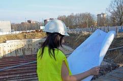 Jonge vrouwelijke architect bij de bouwwerf van het bouwproject royalty-vrije stock afbeeldingen