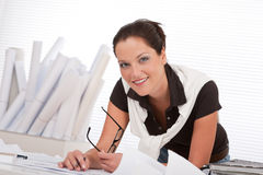 Jonge vrouwelijke architect met plannen op het kantoor Stock Fotografie