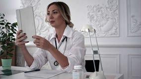 Jonge vrouwelijke arts die door scype op tablet met patiënt in bureau spreken stock videobeelden