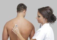 Jonge vrouwelijke arts die een mannelijke patiënt onderzoekt Stock Foto