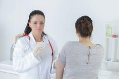 Jonge vrouwelijke arts die injectie geven in wapen Royalty-vrije Stock Afbeelding