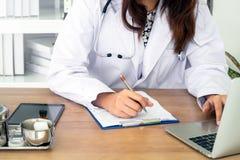 Jonge vrouwelijke arts die laptop met behulp van royalty-vrije stock afbeelding