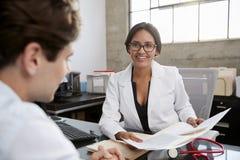 Jonge vrouwelijke arts die mannelijke geduldige documenten in bureau tonen royalty-vrije stock foto