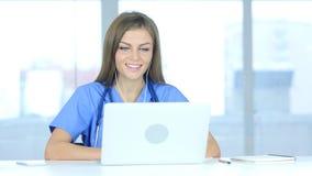 Jonge vrouwelijke arts die met geduldig, online videopraatje op laptop spreken royalty-vrije stock foto