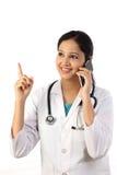 Jonge vrouwelijke arts die op mobiele telefoon spreken Stock Fotografie