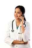 Jonge vrouwelijke arts die op mobiele telefoon spreken Royalty-vrije Stock Afbeelding