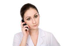 Jonge vrouwelijke arts die op telefoon spreekt Stock Foto's